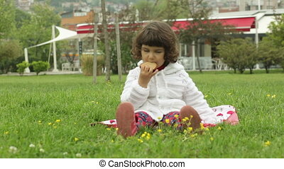 little girl sits on a lawn and eats a piece of cake