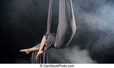 Silk Hammock - Yoga practitioner sitting in hammock formed...