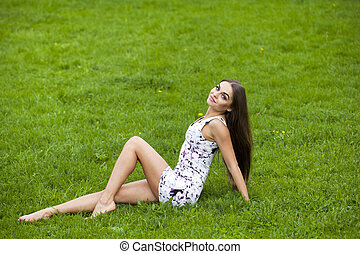 Sexy woman in short dress sitting on green grass - Sexy...