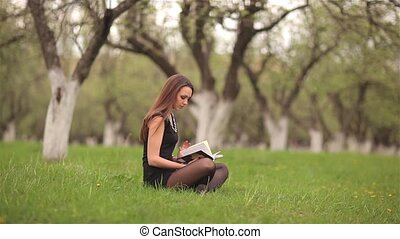 Girl reading a book on green lawn