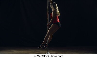 For Men Only - Side view of sexy woman pole dancing...