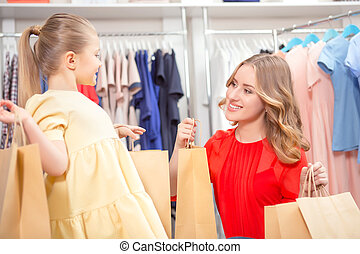 Happy mother with her daughter and lots of new purchases in...