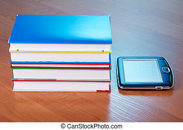 Pile of books, and the pocket electronic book, on a table
