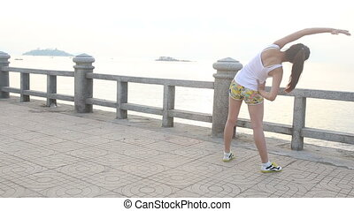 asian girl does exercises on embankment against  city at dawn