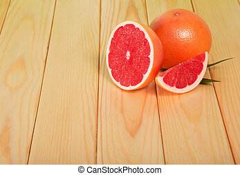 Grapefruits segments on a wooden table, closeup