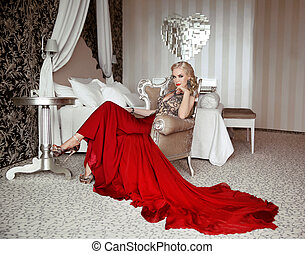Beautiful adult woman in fashion red dress sitting on modern...