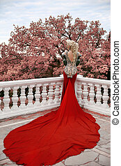 Fashion elegant blond woman model in red gown with long train of dress. Outdoor full length portrait photo.