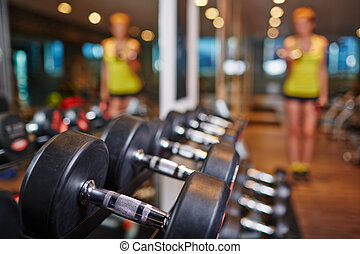 Barbells in sports club - Row of barbells in gym with human...