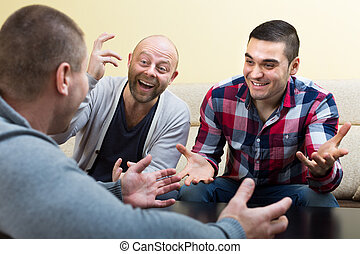 Three male friends talking at home - Three smiling male...