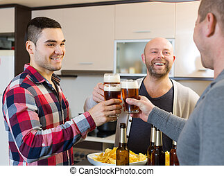 Three guys at house party - Three men drinking beer,eating...