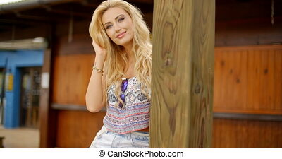 Smiling Blond Woman Sitting on Railing - Smiling Blond Woman...