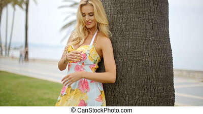 Blond Woman in Sun Dress Leaning Against Palm Tree