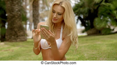 Blond Woman in White Bikini Using Cell Phone - Waist Up of...