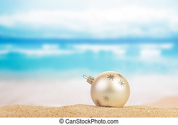 Christmas ball on yellow sand and sea background
