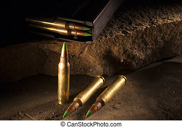 Three cartridges with green tipped bullets and a magazine on...