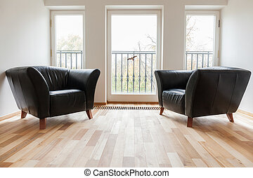Leather black armchairs in a room, horizontal