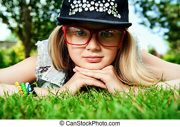 looking to camera - Modern girl teenager lying on a grass in...