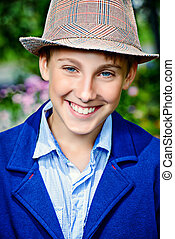 smiling boy - Cool boy wearing hat and jacket stands at a...
