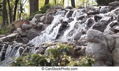 Waterfall cascades flowing over flat rocks in forest...