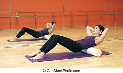 Foam Roller Exercise - Side view of sportswoman lying on the...