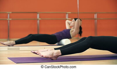 Pilates Class - Dolly along the body of a lady massaging her...