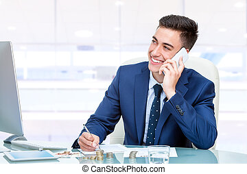 Attractive young businessman talking on smart phone in office