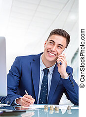 Handsome young  businessman talking on smart phone in office.