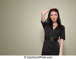 Young beautiful woman in black dress on a grey background