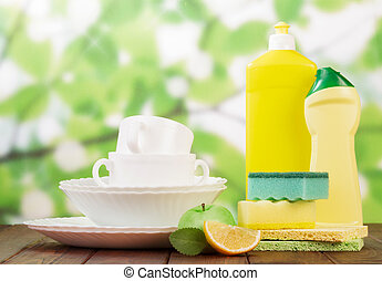 Cleaning products and clean dishes on green background