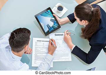 Young business couple discussing rental agreement. Woman...