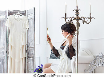 Young bride looks in the mirror. Bridal morning