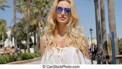 Blond Woman Wearing Sunglasses Outdoors - Waist Up of Blond...