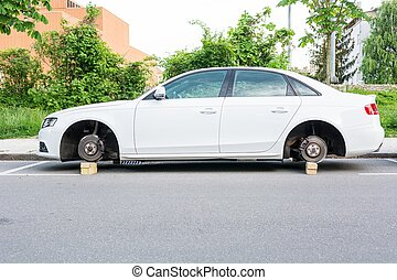 Car with stolen wheels. White vehicle left on wooden bricks.