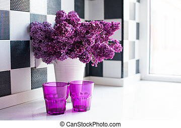 lilacs in a vase and glasses - Spring bouquet of lilacs in a...