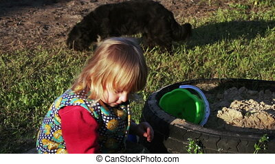 Girl in sandbox - In large wheel sandbox girl playing with...