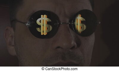 dollar sign reflected in sunglasses on the face of men