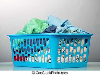 Blue basket with dirty laundry isolated on white
