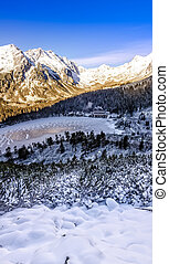 Vertical panoramic view of winter mountains, lake and cottage, Slovakia