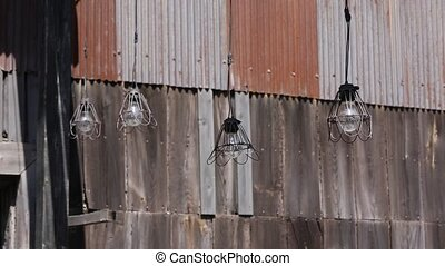 old light bulb in abandoned barn on the wind