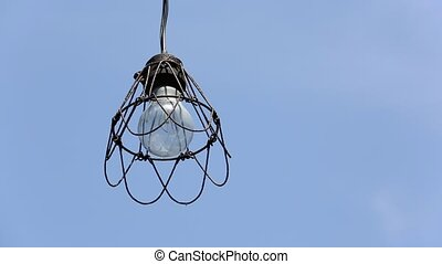 old light bulb against blue sky on the wind