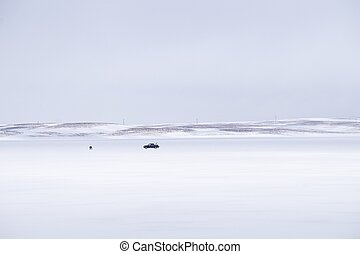 Frozen lake fishing - Lone man doing traditional fishing on...