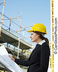 female engineer holding blueprints in construction site