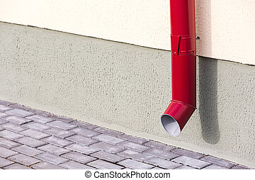 Red drainpipe - Wall of house with red metal downspout and...