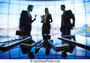 Modern gadgets with pen on background of business group...