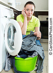 Unhappy girl with dirty clothes near washing machine