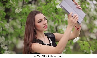 Young woman making selfie on blooming lilac background