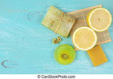 Various natural soaps and lemon on aquamarine wooden...