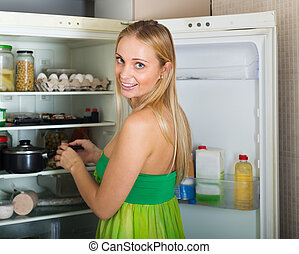 serious girl with money and documents in home kitchen