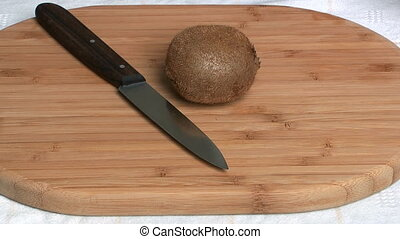 Kiwi on a board. - Kiwi cut by a kitchen knife on a chopping...