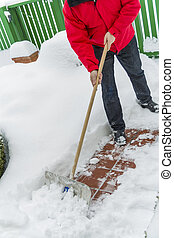 shovel man in snow - a man shoveling snow from a new way...